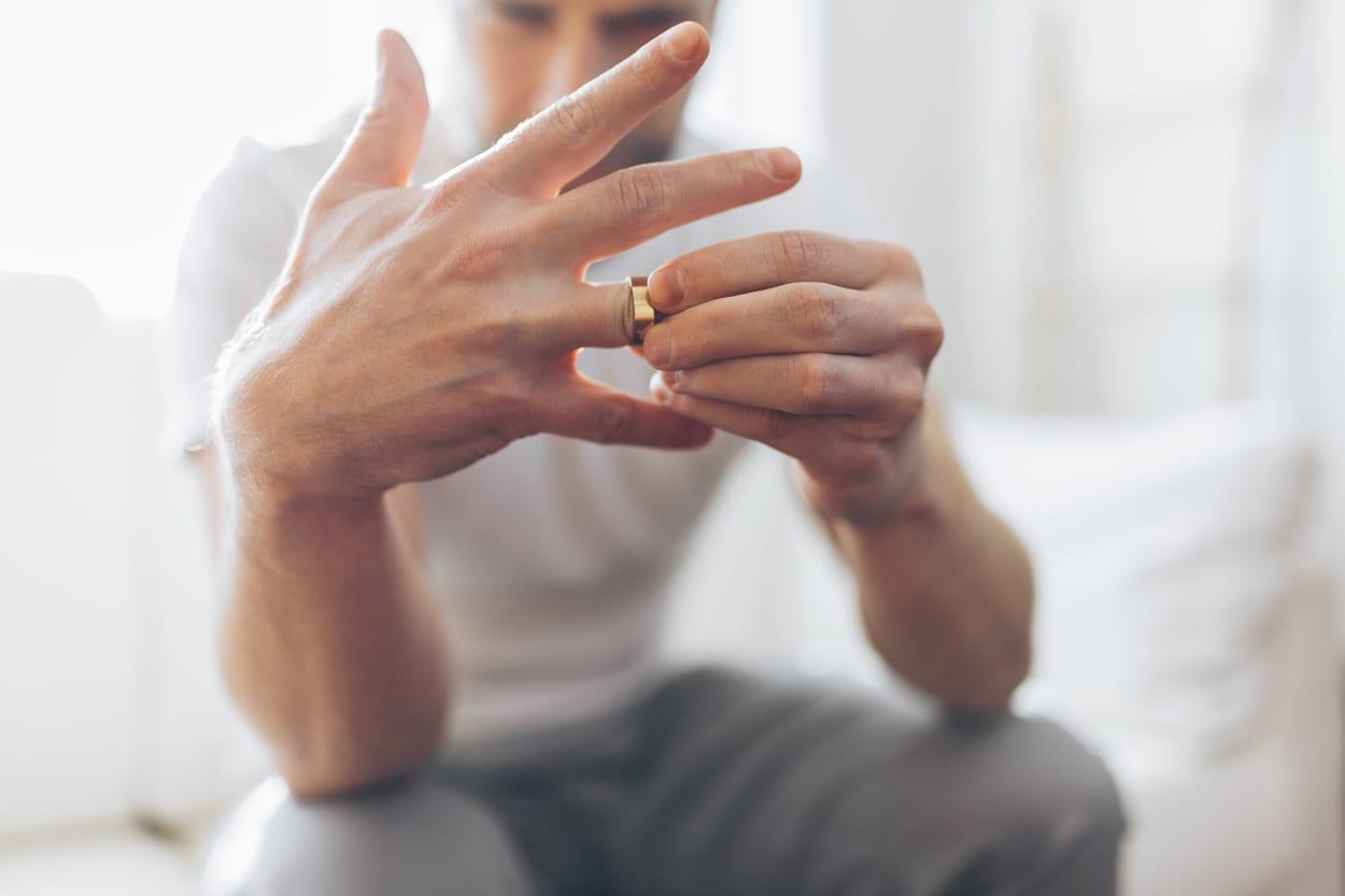 Man taking wedding ring off divorce