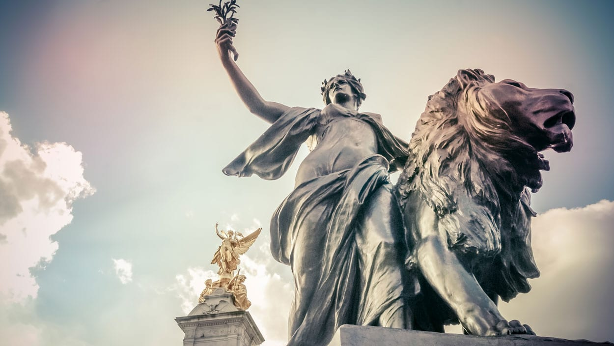 Bronze Statue of the Angel of Justice beneath the gilded figure of Victory on the Queen Victoria Memorial, London, UK
