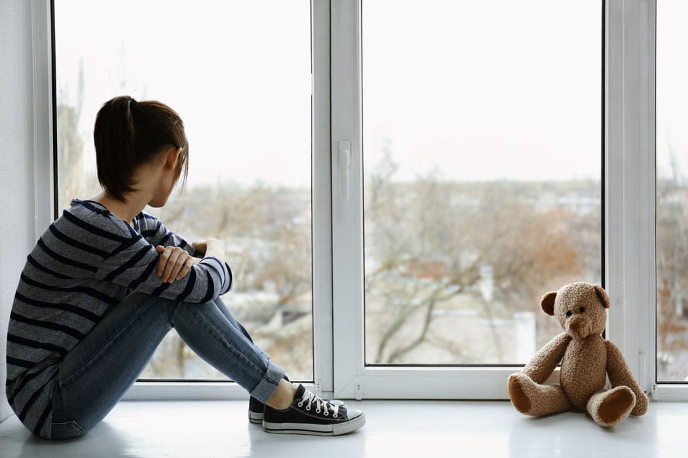 Girl looking out of window separated